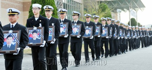 Carrying portraits of the deceased sailors of the Cheonan, naval soldiers walk into the funeral hall in Pyeongtaek, southwest of Seoul, yesterday. Kim Myung-sub/The Korea Herald