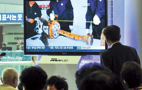 People watch a TV news report on the Cheonan investigation at Seoul Station on Thursday. Kim Myung-sub/The Korea Herald
