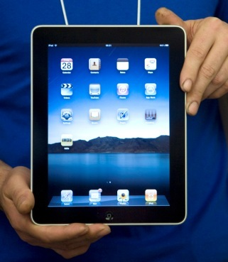 An Apple Inc. iPad tablet computer is held by an Apple employee at the store in London, U.K., on Thursday, May 27, 2010. (Bloomberg)