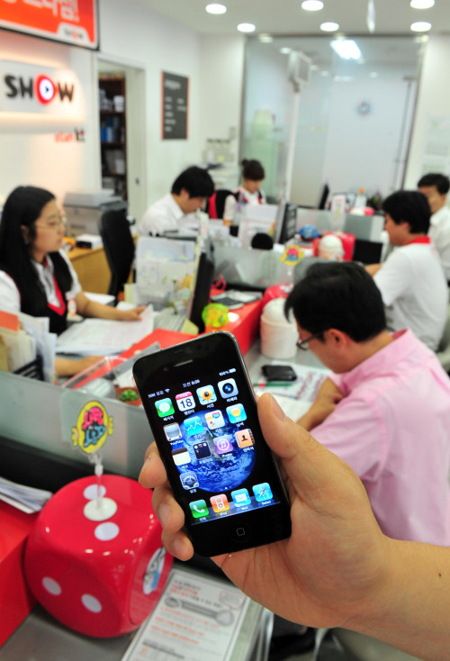 Customers sign pre-order forms for the new iPhone 4 as KT Corp, the exclusive provider ofApple's iPhone, started taking in pre-orders at its website and its branch stores beginningat 6 a.m. Wednesday.(The Korea Herald/Kim Myung-sub)