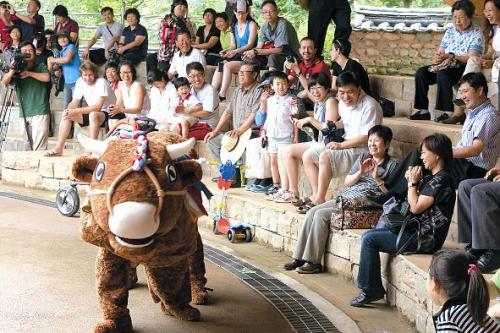 Audience members react as the cow character urinates during the mask dance drama ahoe Byeolsingut Talnori. (Kim Yoon-mi/The Korea Herald)