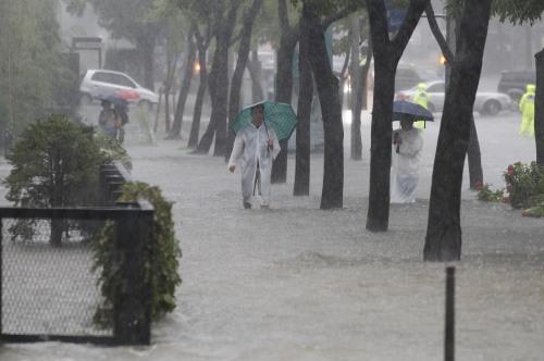 People walk in a heavy rain fall under the Hannam Bridge in Seoul on Tuesday. (Yonhap)