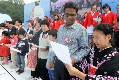 """SING TOGETHER — Multicultural families sing """"You & I"""" at the 2010 Hand in Hand Multicultural Family Festival in Suwon, Gyeonggi Province on Sunday. (Lee Sang-sub/The Korea Herald)"""