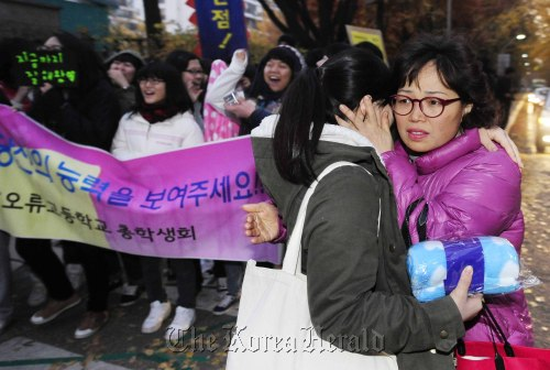 A mother embraces her daughter as family members and fellow students at Yeouido high school give support. (Park Haemook/The Korea Herald)