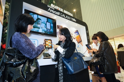 Visitors try Samsung Electronics' Galaxy Tab in its promotional event at a department store in Seoul on Sunday. (Samsung Electronics)