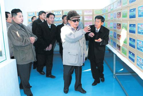This photo released by North Korea's state-run media Thursday shows Kim Jong-il and his son Jong-un (left) visiting a food factory in Pyongyang. (Yonhap News)