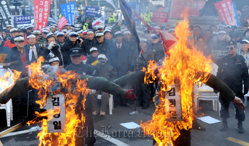 Participants burn effigies of North Korean leader Kim Jong-il and his son Jong-un during a rally against the artillery attack on a South Korean island in Seoul on Monday.(Ahn Hoon/The Korea Herald)