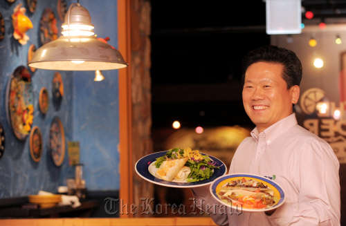 Jimmy Lee, CEO of JRW Inc., operator of On the Border restaurants in Korea, poses with new bulgogi taco and burrito menus at the On the Border restaurant in Samseong-dong in southern Seoul on Dec. 1. (Ahn Hoon/The Korea Herald)