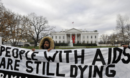 An activist holds a banner during a mock funeral for people who died of the HIV/AIDS in the past year, marking the World AIDS Day and calling for U.S. President Barack Obama to fulfill his promise to fund global AIDS, in front of the White House in Washington D.C., capital of the United States, Dec. 1, (Xinhua-Yonhap)