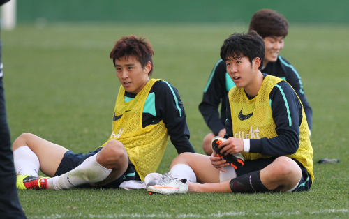 Korean national team midfielder Koo Ja-cheol (left) and Son Heung-min take a break during a training session at the Jeju World Cup Stadium on Wednesday. (Yonhap News)