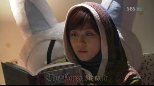 """A scene from """"Secret Garden"""" where actress Ha Ji-won, who plays Gil Ra-im, reads the book """"Alice's Adventures in Wonderland"""" (Captured from SBS)"""