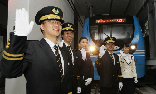 Train officials wave their hands on Tuesday at a ceremony at Seoul Station marking the direct railway linking downtown Seoul with Incheon International Airport. (Yonhap News)