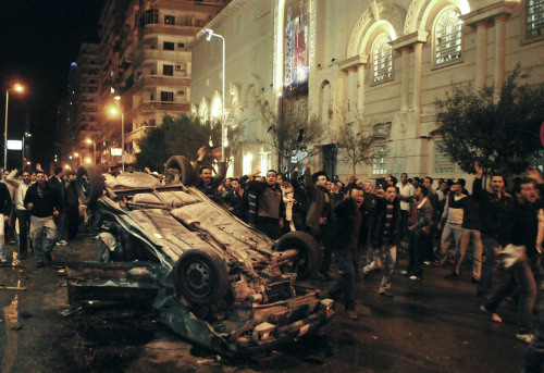 Worshippers shout around an exploded car in front of a Coptic Christian church in the Egyptian city of Alexandria. (AP-Yonhap News)