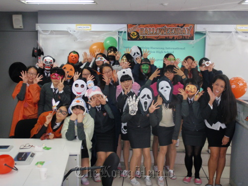 English teacher Jennifer Graham-Magill (right) and her students at Haeseong International Convention High School pose for a picture at a Halloween event in October. (Haeseong International Convention High School)