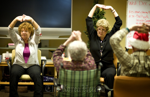 SarahCare owner and CEO Deborah Delaney (second from right) and program coordinator Diane Stang (left) lead a group in a short exercise session on Dec. 22, in Savage, Minnesota. (Glen Stubbe/Minneapolis Star Tribune/MCT)