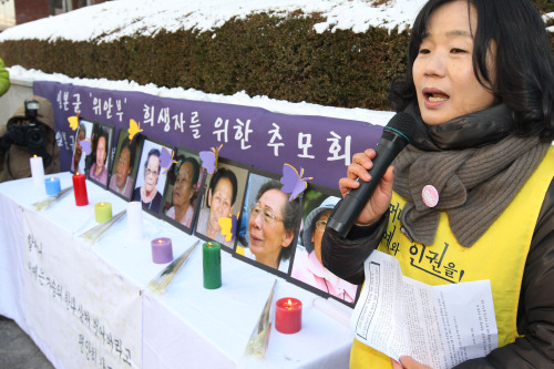 A support group member pays tribute to deceased comfort women at a weekly Wednesday protest in front of the Japanese Embassy in Seoul on Dec. 29. (Yonhap News)