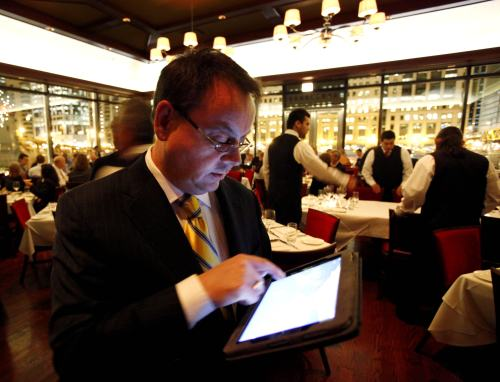 Chicago Cut steakhouse managing partner Matt Moore browses the restaurant's wine list on an iPad in Chicago on Dec. 1. The restaurant is just one of several across the U.S. that have started uploading menus and wine lists to the digital devices. (AP-Yonhap News)