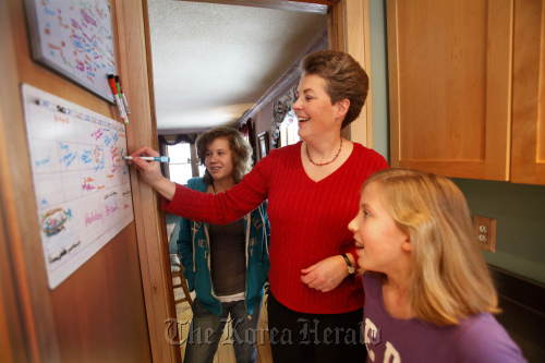People are switching from printed datebooks and calendars to electronic forms, but Ann Mathews-Lingen still keeps important dates written on a kitchen wall calendar for the family to follow. She is shown at home in St. Paul, Minnesota with daughters Emma (left) and Claire. (Minneapolis Star Tribune/MCT)