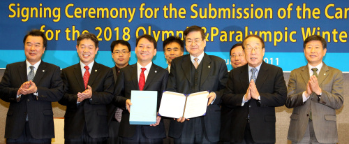Cho Yang-ho (fourth from right), CEO of PyeongChang's 2018 bid committee, Korean Olympic Committee president Park Yong-sung (second from right) and Lee Kwang-jae (fourth from left), governor of Gangwon Province, pose for a photo after signing the finalized 2018 Winter Olympics bid proposal in Seoul on Thursday. (Yonhap News)