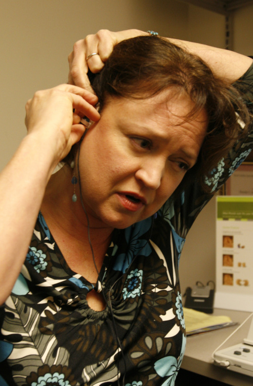 Teri Kim of Cary puts on the two earpieces for her Neuromonics tinnitus treatment during a test session in Duke Hospital's Department of Speech Pathology and Audiology in Durham, North Carolina. (MCT)