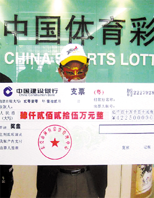The 42-million yuan jackpot winner dressed in a disguise poses for a photo while holding his check, in Dongguan, Dec 31, 2010. [Photo/Guangzhou Daily]
