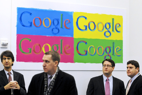 People stand under Google Inc. signage before a news conference at the company's offices in New York, U.S., on Dec. 16.. (Bloomberg-Yonhap)