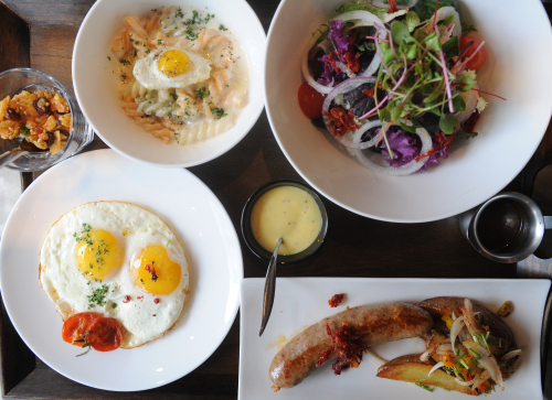 Patrons can get more bang for the buck with Serial Gourmet's brunch set A, which includes a salad, a small bowl of pasta, a large handmade Louisiana-style sausage, wedge-cut fries, eggs, and granola cereal with milk. A small crock of Creole mustard acts as the perfect condiment for the sausage. (Lee Sang-sub/The Korea Herald)