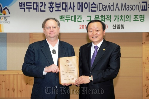 David Mason (left) holds the plaque of appointment as the Baekdu-daegan goodwill ambassador with Forestry Minister Chung Kwang-soo in the Korea Forest Service in Daejeon last Wednesday. (Yonhap News)