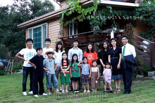 The family of 15 pose for a family photo in front of their house in Gumi.