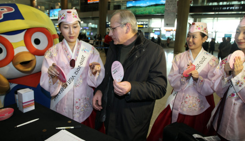 """A foreign visitor receives hotel accommodation vouchers and cultural performance tickets through a lottery at Incheon International Airport on Monday. The seven-day event is part of the shopping festival """"Korea Grand Sale"""" which runs through Feb. 28. (Yonhap News)"""