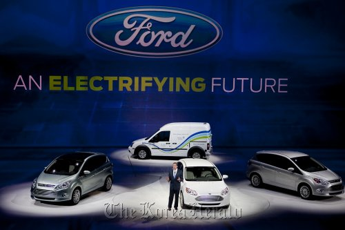 Bill Ford, executive chairman of Ford Motor Co., speaks about electric and hybrid vehicles that will be offered through Ford including (clockwise from left) the C-Max Plug-in Hybrid, the Transit Connect electric van, the C-Max Hybrid, and the Focus Electric, during the North American International Auto Show in Detroit on Monday. (Bloomberg)