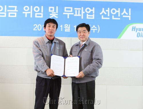 Hyundai Oilbank Co. CEO Kwon Oh-gap (right) receives power of attorney from labor union head Kim Tae-kyeong in Seoul on Wednesday. The firm's union voluntarily waived their right to be involved in a wage negotiation this year. (Hyundai Oilbank Co)