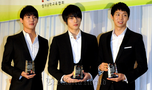 JYJ members Kim Jun-su (left), Kim Jae-joong (center) and Park Yoo-chun hold commemorative plaques at the appointment ceremony as goodwill ambassadors for the robot competition FLL KOREA in Seoul on Thursday. (Park Hyun-koo/The Korea Herald)