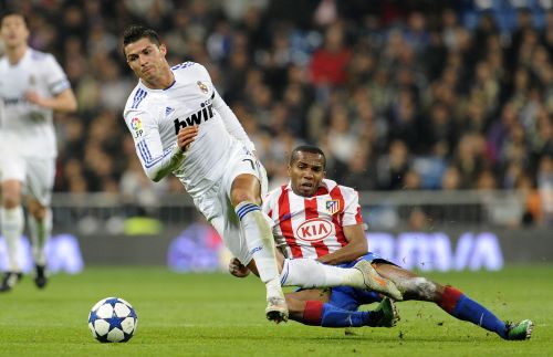 Real Madrid's Portuguese forward Cristiano Ronaldo (left) vies with Atletico Madrid's Brazilian midfielder Paulo Assuncao (right) during the Copa del Rey (King's Cup) football match Real Madrid CF vs Club Atletico de Madrid on Thursday at the Santiago Bernabeu stadium in Madrid. (AFP-Yonhap News)