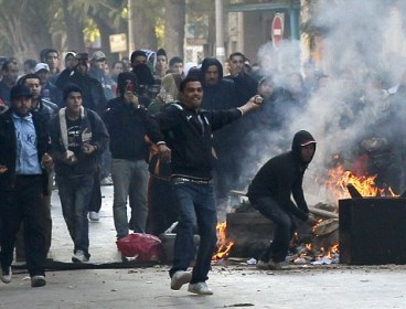 Flames of hate: Hordes of protesters against the president hurl rocks at police yesterday during clashes on the streets of Tunis. (AP-Yonhap)