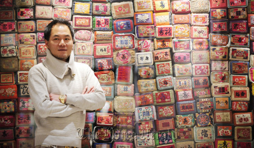 Traditional hanbok designer Kim Young-seok poses in front of a mosaic wall stacked with traditional pillows of his design at his boutique. (Park Hae-mook/The Korea Herald)