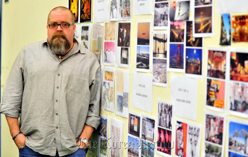 """David Gallo, New York-based stage designer, stands against the wall of concept photos for the musical """"Tears of Heaven"""" at a practice studio in Seoul on Wednesday. (Kim Myung-sub/The Korea Herald)"""