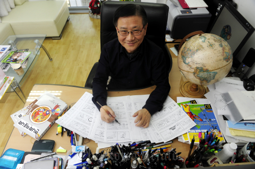 """Prof. Rhie Won-bok works on his """"China"""" series comic strip for a newspaper in his workroom. (Park Hae-mook / The Korea Herald)"""