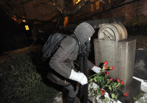 Edgar Allan Poe fan Cynthia Pelayo of Chicago lays roses near the author's original burial place Wednesday at Westminster Church and Cemetery in Baltimore. (AP-Yonhap News)