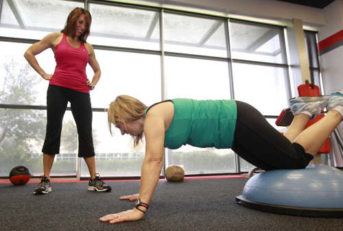 One key to sticking with exercise is finding a workout that you enjoy, says Lori Johnson, working out with client Elaine Taylor at Snap Fitness in Dallas, Texas. (MCT)