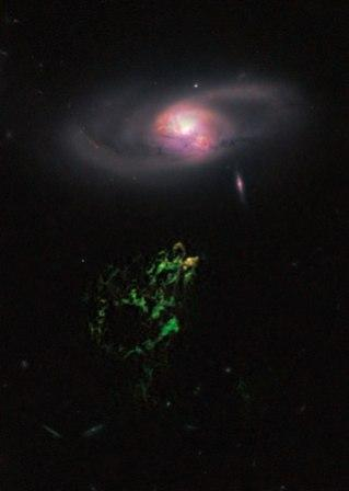 This handout photo provided by NASA, taken April 12, 2010 by the Hubble Space Telescope, shows an unusual, ghostly green blob of gas appears to float near a normal-looking spiral galaxy. (AP-Yonhap News)