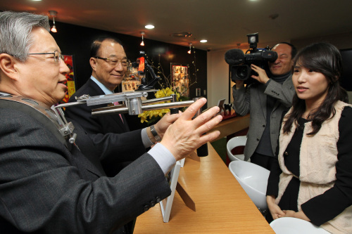 Korea Communications Commission chairman Choi See-joong (second from left) and KT chairman Lee Suk-chae (left) test the supplementary devices which enable the shooting of images with mobile phones at the launching ceremony of KT's Olleh media center in southwestern Seoul on Wednesday. (Yonhap News)