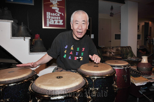 Jazz percussionist Ryu Bok-sung plays the bongos at his basement practice room in Guuidong, Seoul on Monday. (Chung Hee-cho/The Korea Herald)