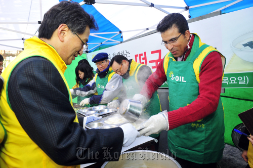 S-Oil CEO Ahmed A. Subey (right) helps out in an event to give free tteokguk, traditional Korean rice cake soup typically eaten on Lunar New Year, to homeless people in a charity event in Seoul on Thursday. (S-Oil)