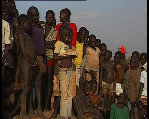 """Emmanuel Jal as a child (in the middle, lifting up his yellow shirt) at the Pinyudo refugee camp in Ethiopia (Captured from the documentary film """"Warchild"""")"""