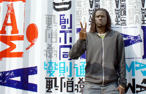 """Emmanuel Jal makes a peace sign in front of Kwai Tsing Theater in Hong Kong, wherethe """"Make a Difference"""" forum was held last weekend. (Park Min-young/The Korea Herald)"""