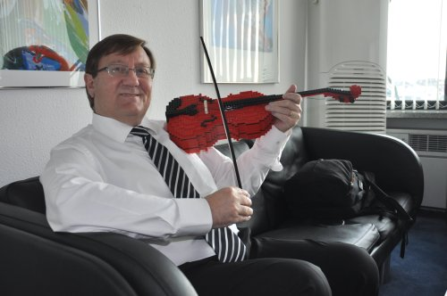Danish Ambassador Peter Lysholt Hansen playsa violin made from Lego parts which could beused for the educational development of youngchildren. (Yoav Cerralbo/The Korea Herald)