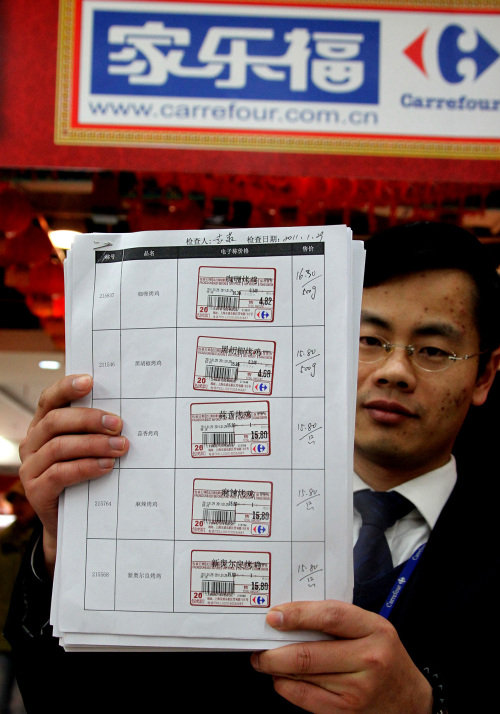 A Carrefour employee presents a re-examined price tag in a store in Shanghai on Sunday. (Xinhua-Yonhap News)