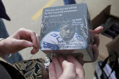 In this photo made Thursday, Jan. 27, 2011, anti-sex trade advocate Jackie Edmonds holds anti-trafficking awareness coasters that her group will ask restaurants to use near the Super Bowl site in Arlington, Texas. Cities that host the big game often attract a bustling sex trade, and this year Texas authorities and advocacy groups are stepping up their anti-prostitution efforts, especially where young girls are concerned. (AP-Yonhap)