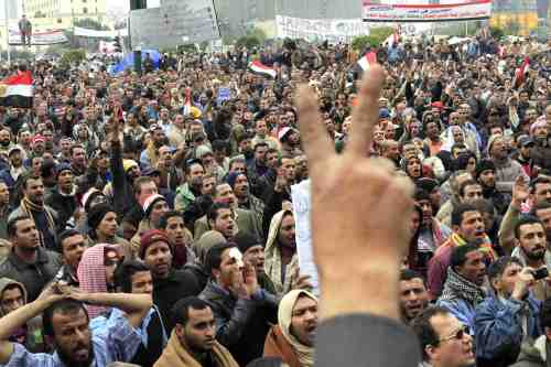Egyptian anti-Mubarak protesters shout slogans and flash V-signs during their protest in Cairo on Saturday. (AP-Yonhap News)